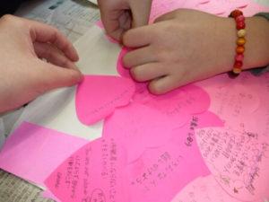ピンク色のハート型の紙にメッセージを書く女子生徒の手