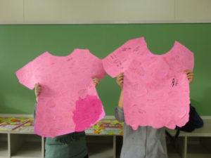 メッセージが書かれたピンクTシャツ型の大きな紙を持つ二人の女子生徒