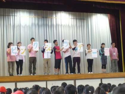 小学校の体育館の舞台上に立って演説する小学生たち