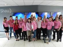 大型スクリーン前でピンクシャツを着て集合写真を撮影するニュースキャスターたち