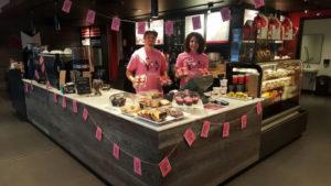 ピンクシャツデーいじめ反対運動のためにピンクのカップケーキを用意するカフェ従業員