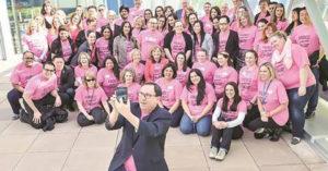 ピンクシャツを着た大勢の人たちの写真撮影