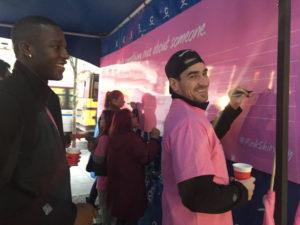 ピンクシャツを着てボードにメッセージを書き残すスポーツ選手