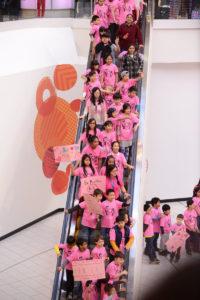 ピンクシャツデーいじめ反対運動のためにピンクシャツを着てモールでダンスを踊るこどもたち