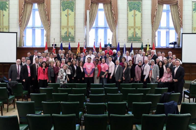 ピンクシャツを着て集合写真を撮影するカナダ国会議員たちとカナダ首相