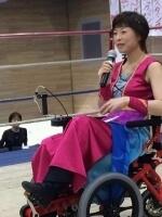 車いすに座りマイクを持ってスピーチする女性