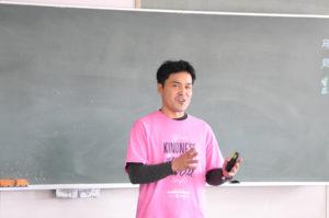 教壇に立って小学生たちを前に説明する男性