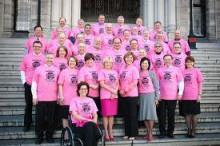 ピンクTシャツを着た州政府の議員たちの集合写真