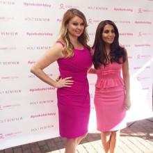 ピンクのワンピースを着てインタビューするキャスター