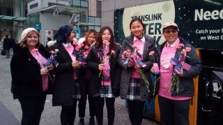 ピンク色のカーネーションを配る学生たち