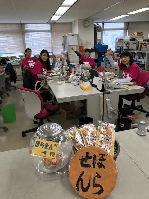 ピンク色のTシャツを着て着席しているボランティアセンターのスタッフたち