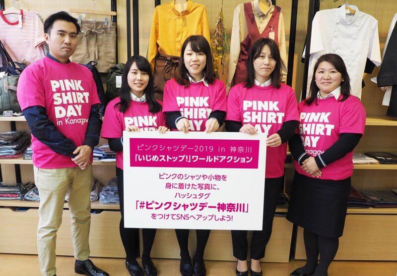 ピンク色のTシャツを着て働く社員たち