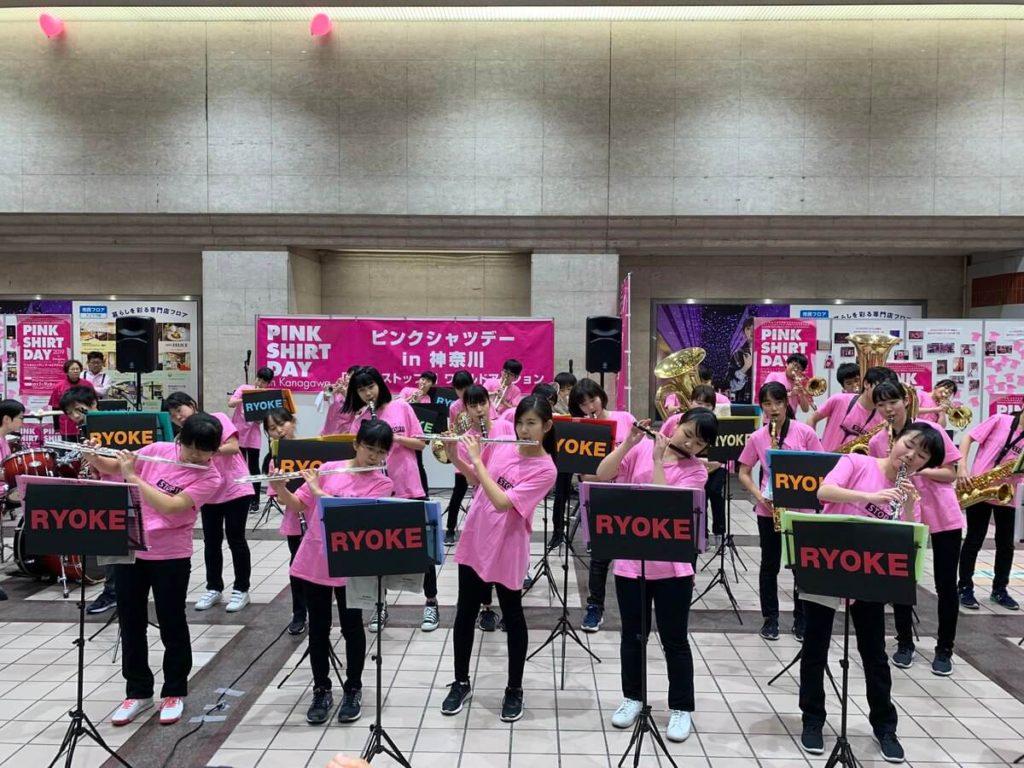 ピンクシャツを着用して演奏する中学校の吹奏楽部の生徒たち
