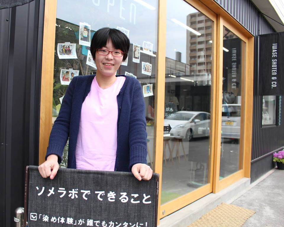 ピンクシャツを着て看板の前に立つ女性