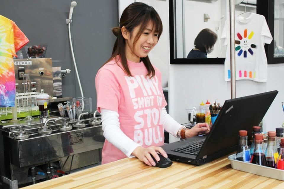 ピンクシャツを着てパソコンを操作する女性社員