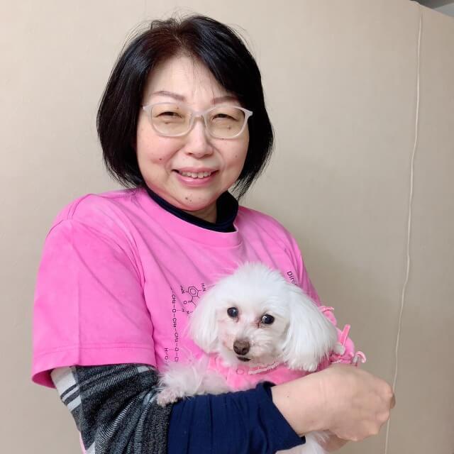 ピンク色の服を着た犬とピンクTシャツを着た女性