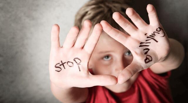 手のひらに描かれたstopbullyingの文字を見せる少年