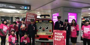 駅構内の電子看板の前で集合写真を撮影するピンクシャツ着用の社員のみなさまと車掌さんたち