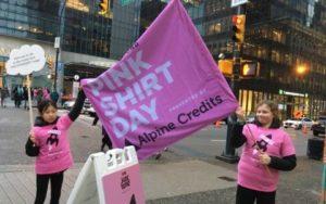 ピンクシャツデーと書かれたピンク色の旗を掲げて、いじめ反対と募金をよびかけるボランティアの子供たち